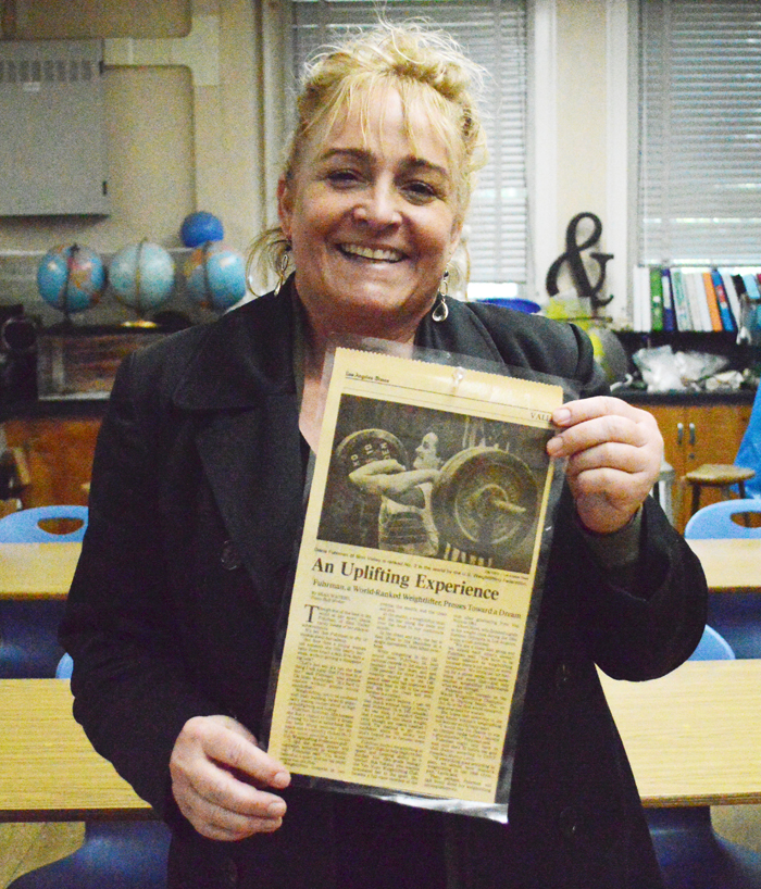 Ms. Fuhrman holds a newspaper featuring her earlier days as a weightlifter.