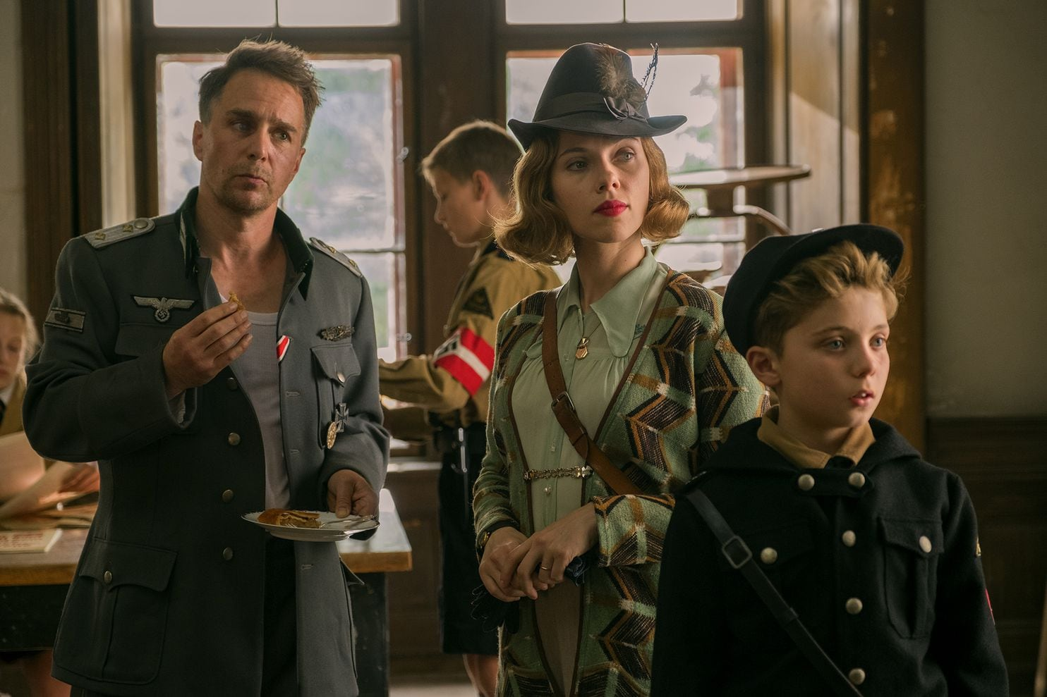 Captain Klenzendorf (Sam Rockwell) with Rosie (Scarlett Johansson,) Jojo's (Roman Griffin Davis) single mother and Jojo in the film Jojo Rabbit.