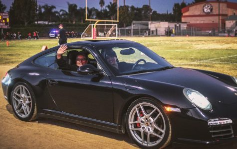 Being sponsored by Keyes, Ms. Gardea(l) and Ms.Dulkanchainun(r) are riding around in a Porche 911 around the football field waving cheerfully at the crowd.