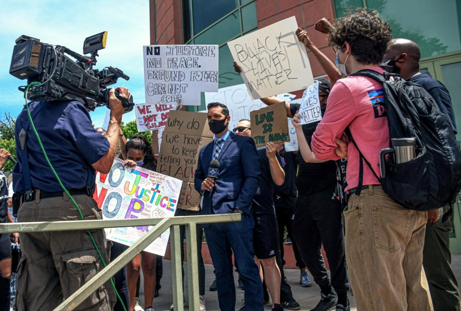 Protestors gather around EstrellaTV news reporter José Luis Muñoz while shouting Black Lives Matter chants to distract Muñoz from reporting the event and preventing the news outlet twisting the story according to an anonymous protestor at Van Nuys City Hall on June 1, 2020.