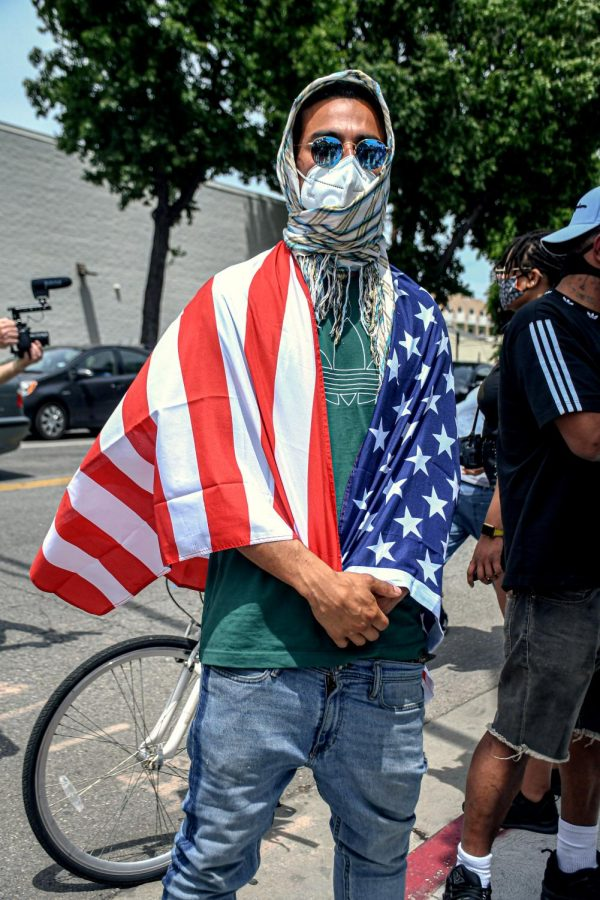 Protestor wears the American Flag as a cape to represent his faith for the US to seek for a change at Van Nuys City Hall on June 1, 2020.