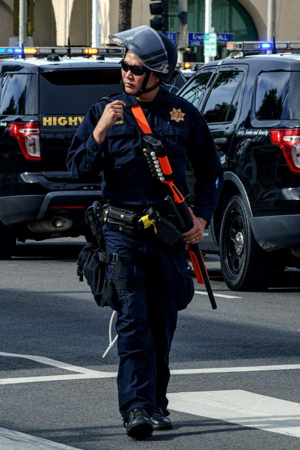 LAPD officer patrols Vesper Ave. while holding a shotgun loaded with rubber bullets on June 1st.