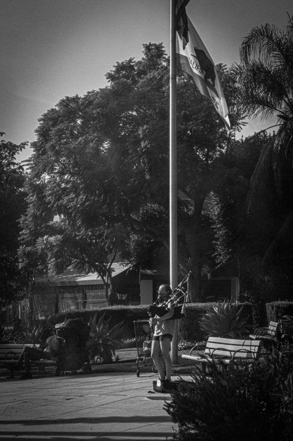 Entertainer is playing the national anthem with their bagpipe by the pole with the flags of the United States and California in West Hollywood on Election Day. (NOV 3, 2020)