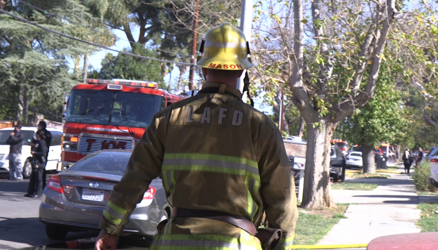 Firefighter walking on sidewalk to confirm that the fire has not spread any further.