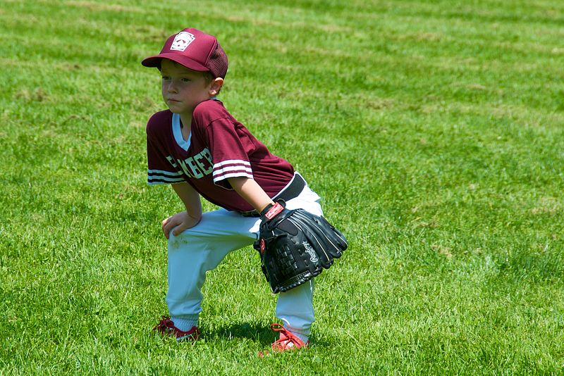 A little league baseball player waiting for the next batter to send a ball his way.
