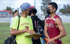 Track and Field Coach Fernando Fernandez speaks to runner Uriel Ruiz after a relay race. Both are wearing masks and following covid-19 guidelines.