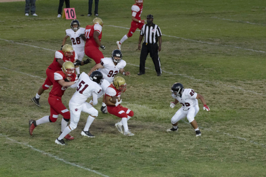 Taft's offense carries the ball as Eduardo Camarena (#51) and two others prepare to tackle.