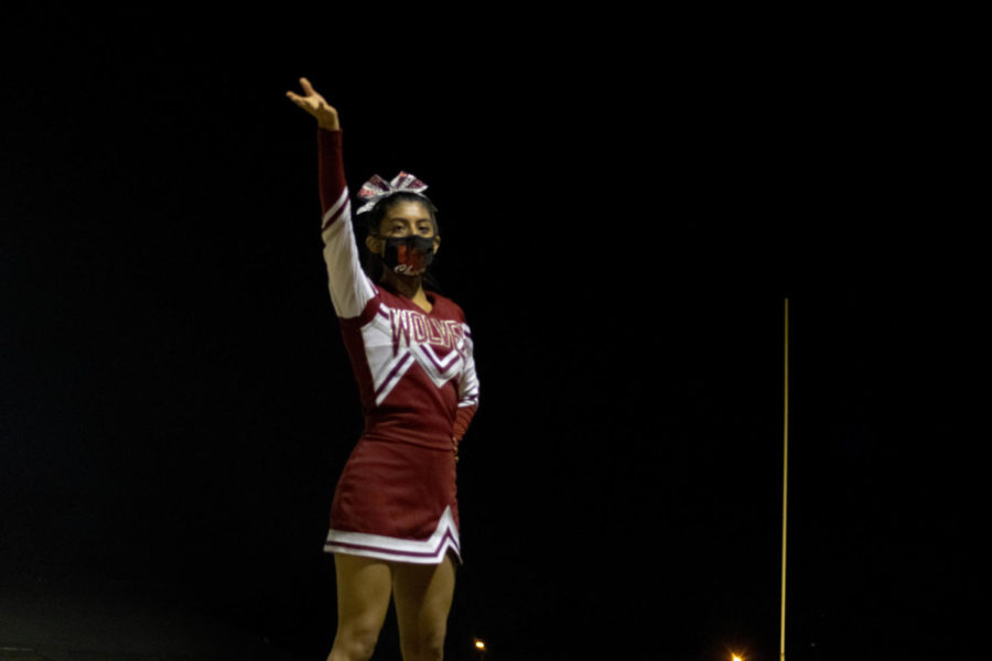 Senior cheerleader, Evelyn Clara-Cantoran looks comfortable at the top, as she cheers on her team from the sides.