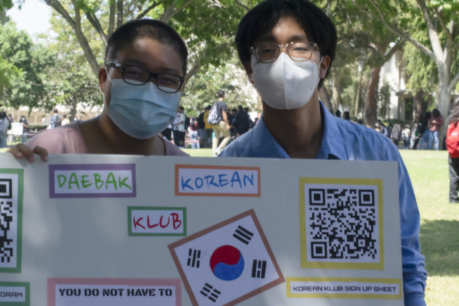 The Korean Club stands in front of their colorful poster on the quad during lunch.