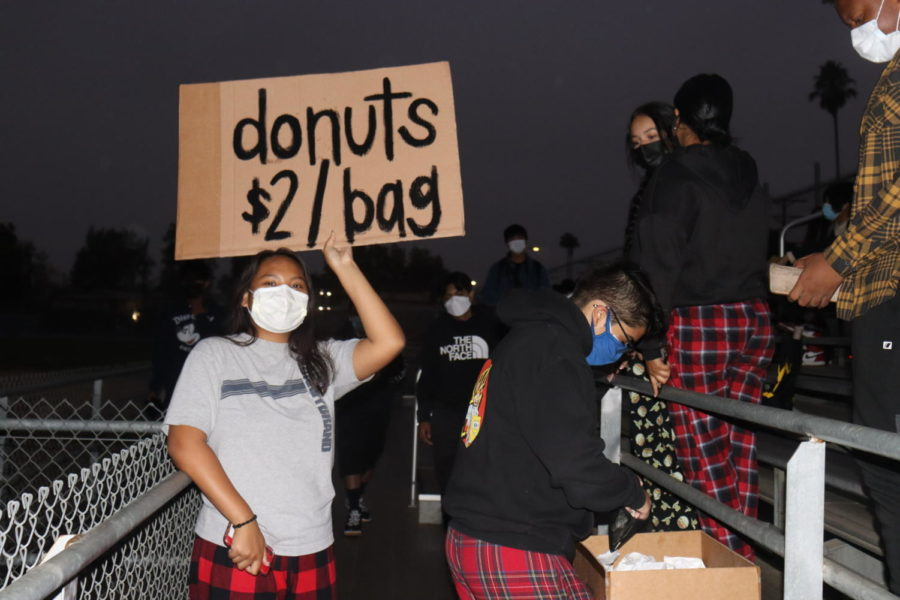Asb member Rona Lasam advertises for donut holes as seniors filled the stands on the west side of the football field.