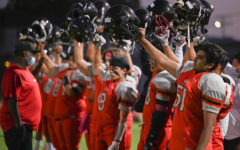 The VNHS wolves raise their helmets in the air during the national anthem to kick off the homecoming game. The Homecoming game on Oct. 2, 2021 ended in a defeat for the home team 35-8 against Panorama.