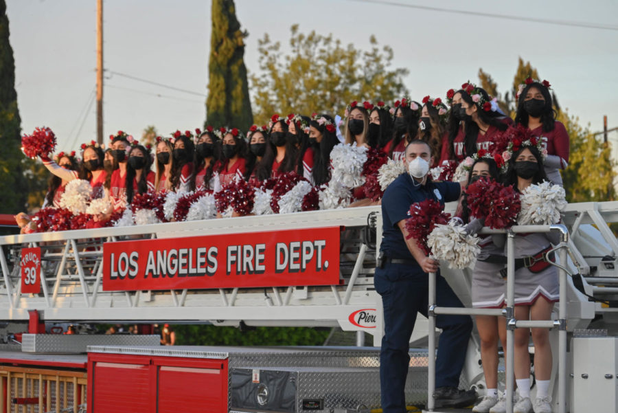 The cheer team gets in position on the firetruck for the parade.