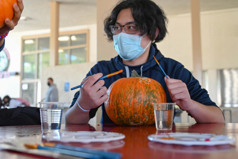 After choosing his perfect pumpkin, Senior Marvin Ocampo prepares a scary idea to paint.