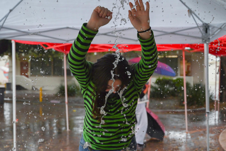 Senior Angela Proca dances under the tents on the quad and tries to avoid getting drenched.