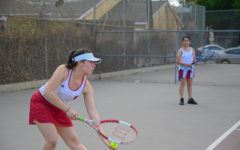 CATS VS. DOGS: Jacqueline Recinos prepares to serve the ball to her opponent on the San Fernando Tigers as Ariel Gutkin, her doubles partner, waits on the side. The Wolves lost their final home game 5-2.