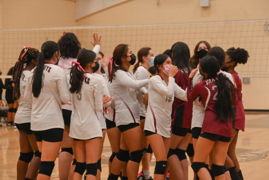 The girls volleyball team huddles for a celebration, just after scoring the winning point.