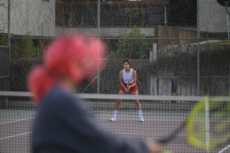 Jasmine Cheysobhon watches her opponent and prepares to receive her serve. In the match, all players were battling the dust kicked up by the strong winds.